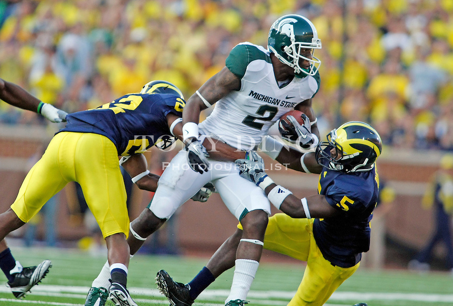 Michigan cornerback Terrence Talbott (22) and safety Vladimir Emilien (5) tackle Michigan State wide receiver Mark Dell (2) in the fourth quarter of an NCAA college football game, Saturday, Oct. 9, 2010, in Ann Arbor. Michigan State won 34-17. (AP Photo/Tony Ding)