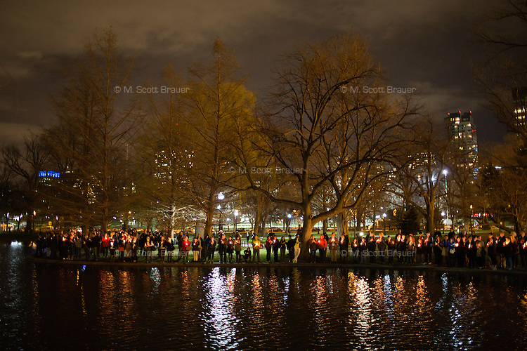 People gather around the lagoon in the Public Garden at Boston Common in Boston, Mass., for a candlelight vigil on April 16, 2013, the day after bombings at the Boston Marathon.