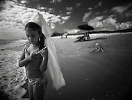 A little girl stands on the beach dressed as a princess