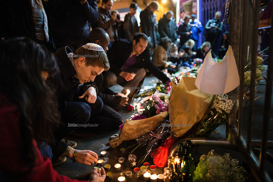 Paris, France, 14.11.2015. Luca Pisano kneels at the site of the Bataclan massacre in central Paris. Images from Paris in the aftermath of the devastating terror attacks on friday november 13. Photo: Christopher Olssøn.