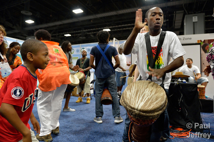 A boy enjoys a man's drumming during a gathering in the Faith Zone of the Global Village at the XIX International AIDS Conference in Washington, D.C.  The Faith Zone was sponsored by the Ecumenical Advocacy Alliance.