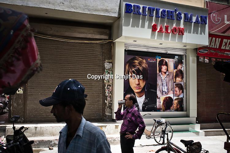 Pedestrians wait to get a glass of water outside a kitsch salon in Uttam Nagar, New Delhi, India. Photo: Sanjit Das/Panos