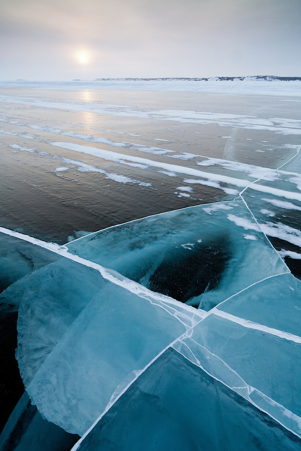 The Dettah ice road displays many fractures and cracks from vehicle travel as the sun sets near Yellowknife in the Northwest Territories, Canada.