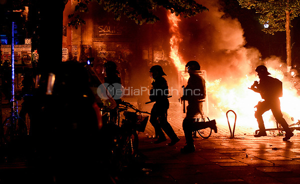 Police in riot gear run past a burning barricade during demonstrations against the G20 summit in Hamburg, Germany, 6 July 2017. Photo: Axel Heimken/dpa /MediaPunch ***FOR USA ONLY***
