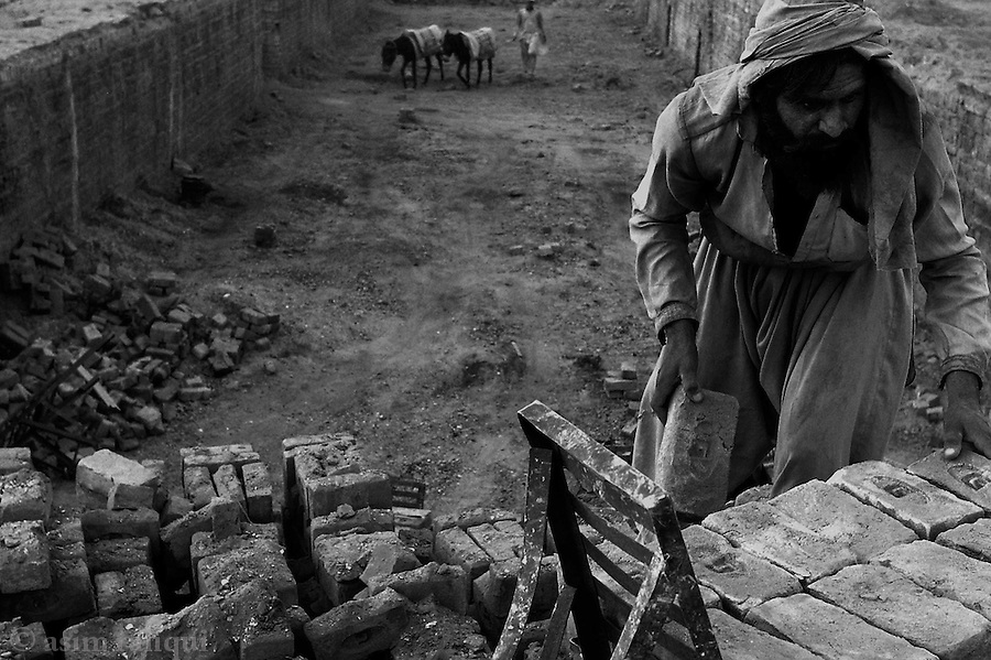 loading prepared bricks for delivery to the markets.  one end of the pit is picked clean of prepared bricks while the other end is refilled with clay/soil that is then baked.  jalozai, peshawar, pakistan.  september 2003&amp;#xA;&amp;#xA;copyright asim rafiqui 2003&amp;#xA;<br />