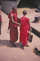 Two Buddhist monks exchange a greeting on the Rangoon River jetty for Kyauktan.