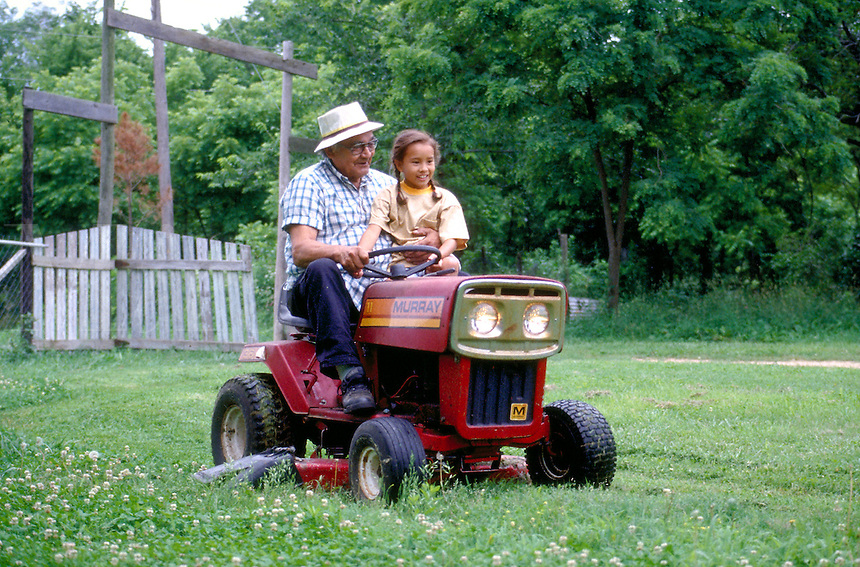 10 year-old Cherokee girl riding on lawnmower with her grandfather,  Tahlequah, OK