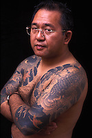 Kaoru Inoue poses for a photograph, showing his tatoos remarking his history of being a member of the Japanese mafia Yakuza before becoming a devoted Christian with the Protestant Evangelical group Mission Barabbas in Tokyo, Japan.