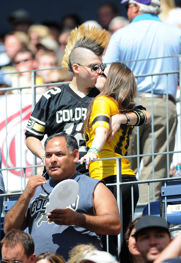 SEPTEMBER 17, 2011:  A pair of Colorado Buffaloes fans, including a man with a mohawk, kiss in the stands dressed in school colors   during an inter-conference game between the Colorado State Rams and the University of Colorado Buffaloes at Sports Authority Field at Mile High Field in Denver, Colorado. The Buffaloes led 14-7 at halftime*****For editorial use only*****