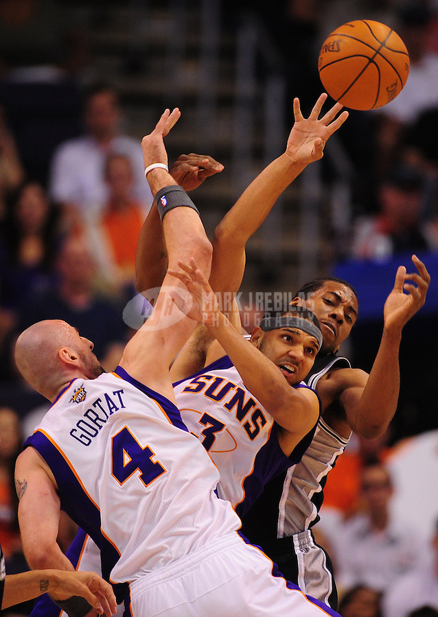 Apr. 25, 2012; Phoenix, AZ, USA; Phoenix Suns center (4) Marcin Gortat and forward (3) Jared Dudley battle for a loose ball against San Antonio Spurs guard (2) Kawhi Leonard in the first half at the US Airways Center. Mandatory Credit: Mark J. Rebilas-