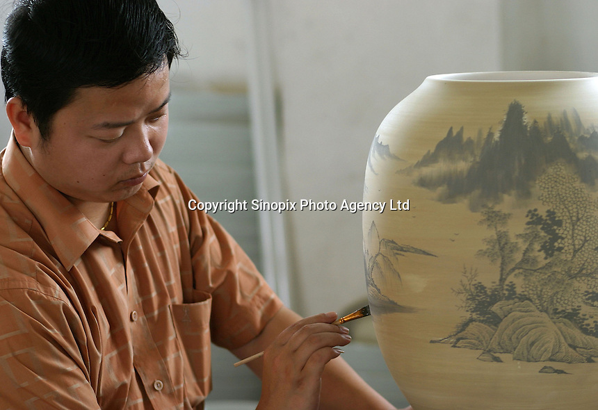 A Chinese worker paints traditional Chinese water color scenes onto a clay vase at a porcelain workshop in Jingdezhen, Jiangxi Province, China. The township of Jingdezhen is well known in China as the country's porcelain capital ever since it was selected exactly one thousand years ago as the royal porcelain provider for the imperial court..24-JUN-04