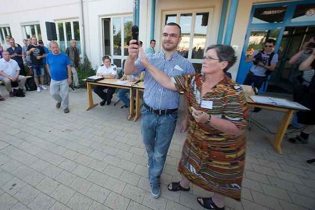 Auf einer Buergerversammlung mit ca. 500 Teilnehmern im Berliner Plattenbaubezirk Hellersdorf entlud sich am Dienstag den 9. Juli 2013 der blanker Rassismus gegen eine geplante Unterkunft fuer syrische Buergerkriegsfluechlinge. Etwa 2/3 Anwesende aeusserten, es solle &quot;zuerst was fuer Deutsche getan werden&quot;, &quot;das Heim anzuenden&quot;, &quot;Wer sein Heimatland verlaesst ist ein Verraeter&quot;, &quot;Wer denkt an unsere Kinder&quot; und aehnliche Parolen gegen das Fluechtlingsheim. Veranstaltungsteilnehmer, die Verstaendnis fuer die Buergerkriegsfluechtlinge aeusserten, wurden niedergebruellt.<br />Im Bild: Der Fuehrer der NPD-Berlin, Sebastian Schmidtke versuchte sich das Microphon zu nehmen und zu den Anwesenden zu reden. Die wurde jedoch unterbunden.<br />9.7.2013, Berlin<br />Copyright: Christian-Ditsch.de<br />[Inhaltsveraendernde Manipulation des Fotos nur nach ausdruecklicher Genehmigung des Fotografen. Vereinbarungen ueber Abtretung von Persoenlichkeitsrechten/Model Release der abgebildeten Person/Personen liegen nicht vor. NO MODEL RELEASE! Don't publish without copyright Christian-Ditsch.de, Veroeffentlichung nur mit Fotografennennung, sowie gegen Honorar, MwSt. und Beleg. Konto:, I N G - D i B a, IBAN DE58500105175400192269, BIC INGDDEFFXXX, Kontakt: post@christian-ditsch.de<br />Urhebervermerk wird gemaess Paragraph 13 UHG verlangt.]