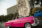 "HAVANA, CUBA -- MARCH 22, 2015:   Tourists drive past the Ministry of the Interior building in the Plaza de la Revolución with Che Guevara's image and slogan ""Hasta la Victoria Siempre"" in Havana, Cuba on March 22, 2015. Photograph by Michael Nagle"