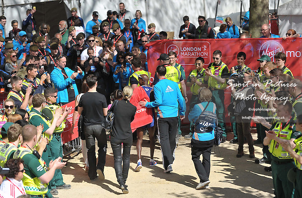 Fans and volunteers applaud and take photos of Mo Farah (GBR) as he is led away at the end of the race. Comedian Jimmy Carr is on Farahs left, dressed in black. Virgin Money London Marathon. London. UK. 13/04/2014. MANDATORY Credit Garry Bowden/Sportinpictures - NO UNAUTHORISED USE - 07837 394578