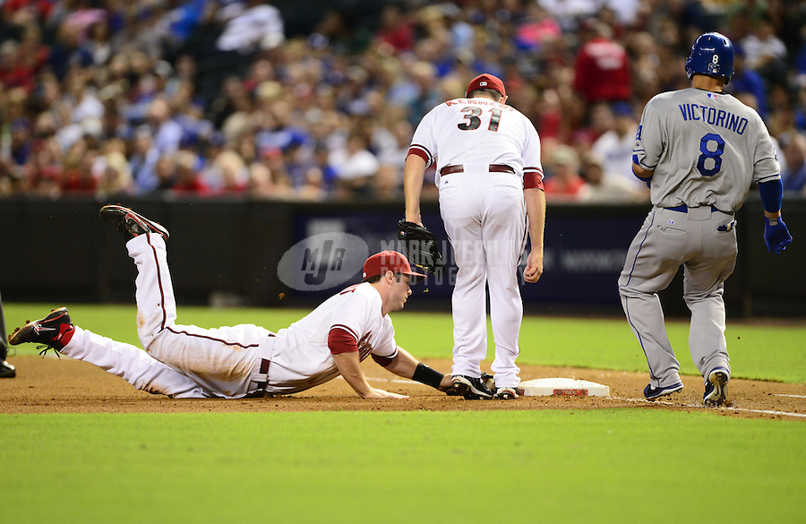 Sept. 11, 2012; Phoenix, AZ, USA: Arizona Diamondbacks first baseman Paul Goldschmidt dives into first base to force out Los Angeles Dodgers base runner (8) Shane Victorino in the fourth inning at Chase Field. Mandatory Credit: Mark J. Rebilas-