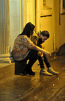 Pictured: A young couple sit on the floor in the early hours of New Year's Day. Sunday 01 January 2017<br /> Re: Revellers out celebrating the New Year in the pub and club on Wind Street Swansea