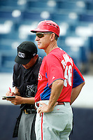 GCL Phillies Rolano de Armas  makes a change with umpire Takahito Matusda during a Gulf Coast League game against the GCL Yankees at Legends Field on July 17, 2012 in Tampa, Florida.  GCL Phillies defeated the GCL Yankees 4-2.  (Mike Janes/Four Seam Images)