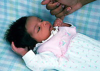 A newborn baby holds the baby finger of a grown up.