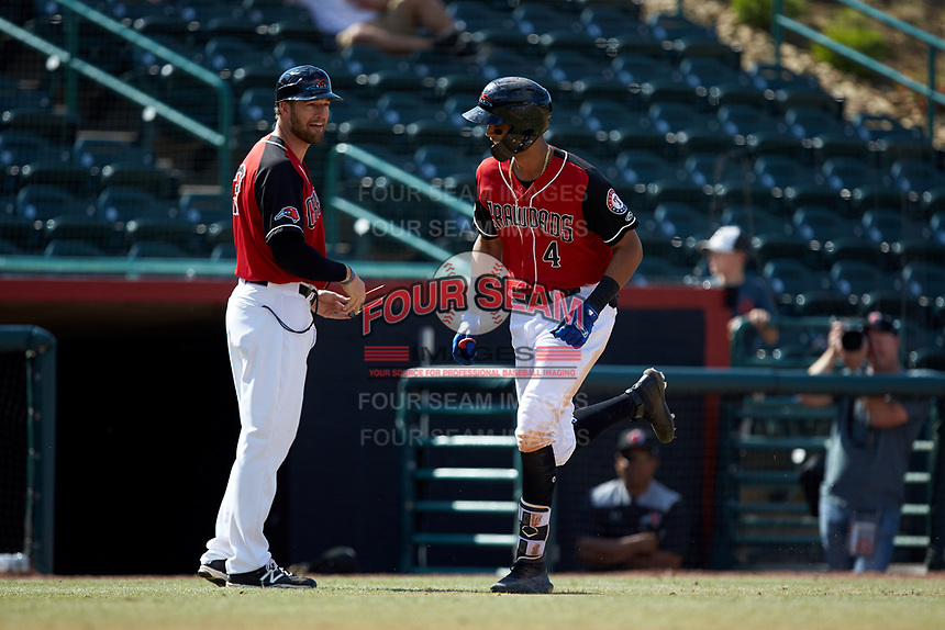 Pedro Gonzalez (4) of the Hickory Crawdads looks at third base coach Matt Hagan (39) as he rounds the bases after hitting a home run against the Lakewood BlueClaws at L.P. Frans Stadium on April 28, 2019 in Hickory, North Carolina. The Crawdads defeated the BlueClaws 10-3. (Brian Westerholt/Four Seam Images)