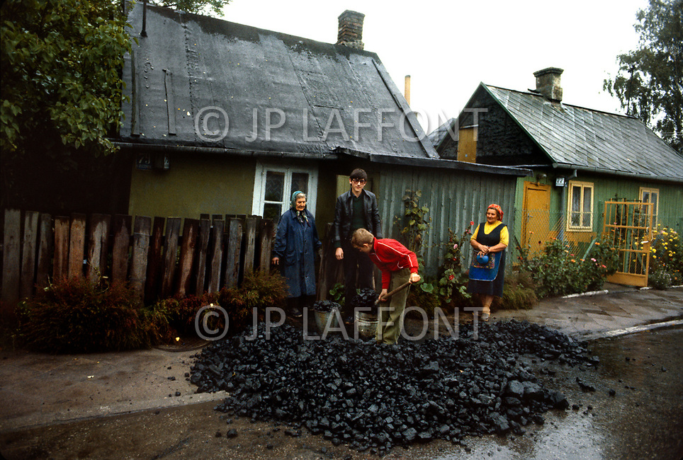 Poland, September, 1981 - In the areas around Warsaw, coal is distributed by truck and dumped in front of people's homes. The residents are responsible for bringing it inside and most have to move it by hand. Coal is the primary source of home heating and fuel for cooking.<br /> Pologne, septembre 1981 &ndash; Environs de Varsovie. Pour se chauffer et faire la cuisine le charbon ne manque pas. Il est distribu&eacute; dans la rue, les habitants se servent selon leur besoin.