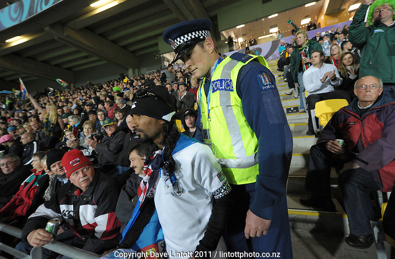 A fans is escorted from the stand during the South Africa versus Fiji pool D match of the 2011 IRB Rugby World Cup at Wellington Regional Stadium, Wellington, New Zealand on Saturday, 17 September 2011. Photo: Dave Lintott / lintottphoto.co.nz