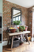 A rustic side table in Kally Ellis's kitchen displays a cheerful arrangement of her florist work and a large fruit bowl