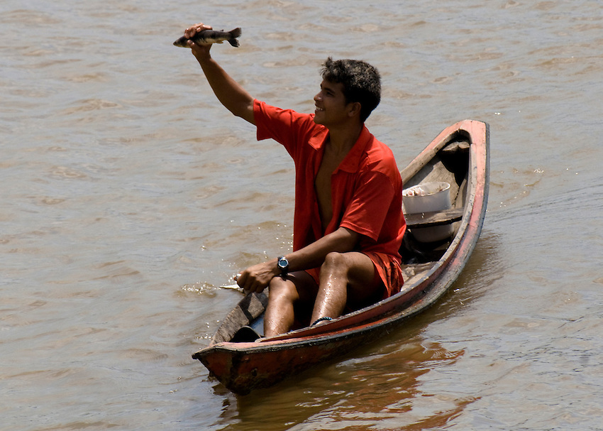 Caboclos, a mix of indigenous Indians and colonizing Portugese, in a dugout canoe on the Amazon River in the Breves Narrows area of Brazil.