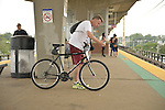 During evening rush hour, a man with his bicycle waits for a train to arrive on elevated platform of Merrick train station of Babylon branch, after MTA Metropolitan Transit Authority and Long Island Rail Road union talks deadlock, with potential LIRR strike looming just days ahead.