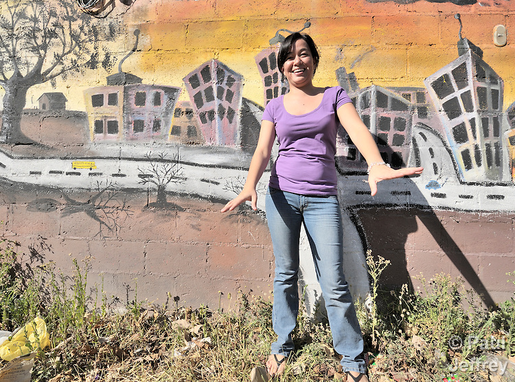 A young woman in San Salvador in front of a street-side mural she helped paint, part of a project sponsored by Quetzalcoatl, a Salvadoran nongovernmental organization.