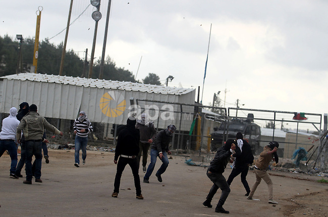 Palestinian students from the University of Birzeit throw stones towards Israeli security forces during clashes following a demonstration in support of Palestinian prisoners on hunger strike in Israeli jails, outside Israel's Ofer military prison, near the West Bank city of Ramallah, on February 12, 2013. Photo by Issam Rimawi