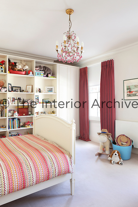 A child's bedroom with built-in storage for displaying a colourful array of toys and books