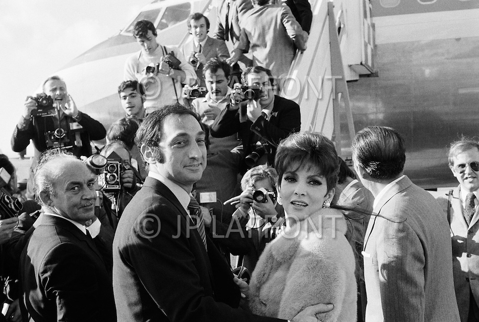 USA. November 16th, 1969. Italian film star Gina Lollobrigida and American businessman George Kaufman surrounded by photographer while boarding and airplane. They plan to marry but Italian law does not recognize divorce and regards her still married to Dr. Miklo Skofic.