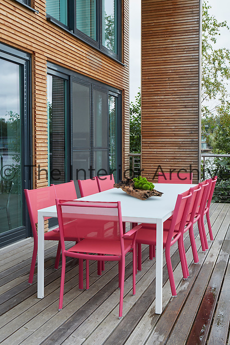 A decked terrace is a perfect spot for alfresco dining. Bright pink dining chairs add a spot of vibrant colour.