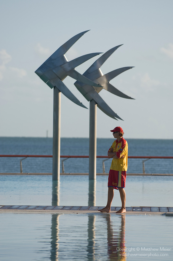 Cairns, Queensland, Australia; a lifeguard stands next to the Cairns Esplanade swimming lagoon, viewed in early morning light, the four megalitres of lagoon water is sourced from the sea and filtered every three hours to keep it clear and clean. Unlike many pools in the southern states of Australia, the Cairns Esplanade lagoon is not tidal. Therefore, no stingers or other marine creatures can enter the pool. Special sand cleaning equipment will frequently scour the surrounding sandy beaches down to a depth of 30cm to remove any foreign objects. , © Matthew Meier, matthewmeierphoto.com All Rights Reserved