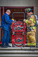 Fire fighters place exhaust fans in the doorway of a building after extinguishing a small electrical fire.