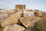 Martello tower defended from erosion by rock armour at East Lane, Bawdsey, Suffolk, England