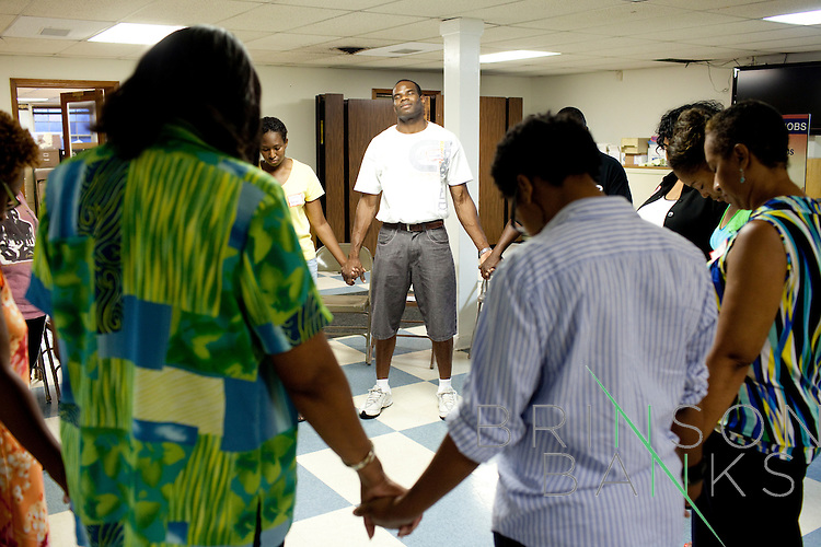 Participants, including Henry Montgomery, Jr. (center), in the Those in Between Jobs meeting led by Marilyn Santiago pray at the beginning and end of the meeting at Ben Hill United Methodist Church in Atlanta, Georgia August 17, 2010. ..Model releases: yes.Utilities Hearing, c/o editor Michael Wichita