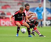 Lincoln City's Michael Bostwick vies for possession with Swindon Town's Scott Twine<br /> <br /> Photographer Chris Vaughan/CameraSport<br /> <br /> The EFL Sky Bet League Two - Lincoln City v Swindon Town - Saturday 11th August 2018 - Sincil Bank - Lincoln<br /> <br /> World Copyright &copy; 2018 CameraSport. All rights reserved. 43 Linden Ave. Countesthorpe. Leicester. England. LE8 5PG - Tel: +44 (0) 116 277 4147 - admin@camerasport.com - www.camerasport.com