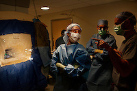 San Francisco, California, January 6, 2011 - From left, Dr. Ellen Air, a clinical fellow, and University of California San Francisco Medical Center neurosurgeon Dr. Philip Starr listen to a question from Dr. Alexander Papanastassiou, a visiting doctor from the University Texas Health Science Center San Antonio, during the iMRI surgery of patient Linda Sharp at UCSF Medical Center.  The iMRI procedure uses Deep brain stimulation (DBS), which has been used for over a decade to treat movement disorders such as Parkinson's disease, essential tremor, and dystonia. DBS uses a pulse generator implanted in the chest, similar to a pacemaker, to deliver pulses to specific regions of the brain via a permanently implanted electrode. In the U.S., DBS is normally done while the patient is awake, because the surgeon needs to induce the symptoms (like the involuntary movements of Parkinson's) to know if he's in the right place, and if the patient is unconscious, the symptoms can't be induced. Many patients find it hard to tolerate. Their head is clamped in a frame, they're aware of their surroundings, and the surgeon is deliberately producing tremors and twitches while they lie there...Interventional MRI (or iMRI) allows surgeons to implant these electrodes while the patient is unconscious taking advantage of MR imaging in real time by performing procedures inside the scanner itself.
