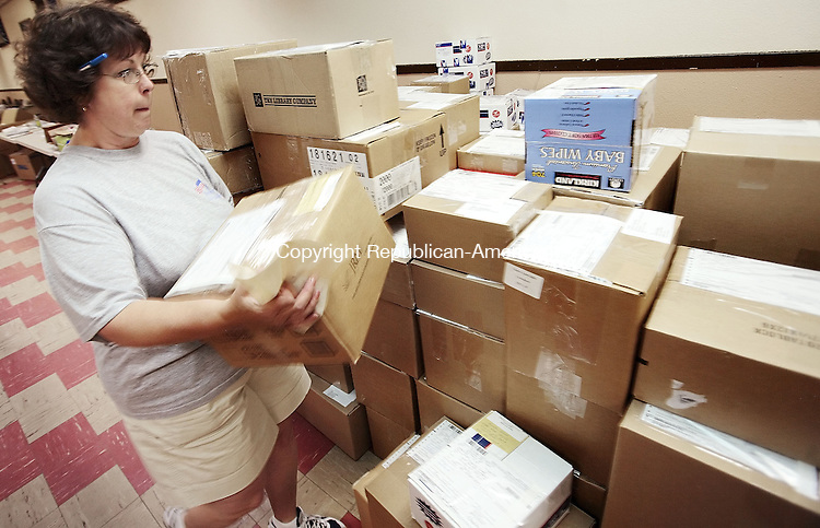 WATERTOWN, CT-- 15 July 2007--07157TJ07- Gaye Zukauskas, from Terryville, a member of the Ladies Auxiliary to the Oakville VFW Post 7330, adds another box to the couple hundred ready to be mailed to troops in Iraq and Afghanistan, during a collection day held by the Ladies Auxiliary on Sunday, July 15, 2007. During the last year, the auxiliary has collected and mailed roughly three tons of supplies to troops overseas. T.J. Kirkpatrick / Republican-American