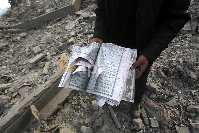 A Palestinian man carry a copy of the holy Quraan at government offices destroyed in an Israeli airstrike in Gaza City, 21 November 2012. Palestinian militants renewed their rocket fire on Israel 21 November and Israel continued pounding targets in the Gaza Strip, as agreement on a hoped-for truce remained elusive. The Israeli military said it bombed around 100 targets in the Strip overnight, including 50 underground rocket launchers. Photo by Ashraf Amra