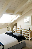 Matching rattan chests of drawers in a bright attic bedroom