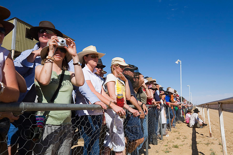 Spectators watch the horse racing action trackside during the Birdsville races. Every September the small town of Birdsville hosts thousands of racing enthusiasts for one of Australia's most famous bush racing carnivals.  Birdsville, Queensland, AUSTRALIA.