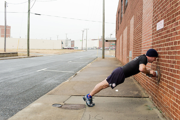 December 22, 2014. Lexington, North Carolina.<br /> Mayor Newell Clark does pushups on a fire department hose attachment.<br />   Newell Clark, the 43 year old mayor of Lexington, NC, leads a group of friends and colleagues on a 4 times a week exercise routine around downtown. The group uses existing infrastructure, such as an abandoned furniture factory, loading docks, stairs, and handrails to get fit and increase awareness of healthy lifestyles in a town more known for BBQ.<br /> Jeremy M. Lange for the Wall Street Journal<br /> Workout_Clark