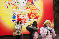 "Some young chinese girls are taking pictures of themselves with a giant drawing of "" a rabbit of fortune"" in the background"" while celbrating the new chinese lunar year 2011. Here in the Ditan park (where the emperor performed the sacrifice yearly for good harvest) during the annual festival for Chunjie."