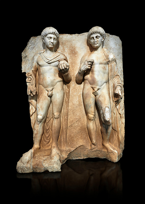 Roman Sebasteion relief  sculpture of  Two princes, Aphrodisias Museum, Aphrodisias, Turkey.  Against a black background.<br /> <br /> Two princes stand like statues, naked, wearing cloaks. The left figure holds the orb of the world in one hand, a symbol of  world rule that indicates he is the imperial heir, and in the other a ship's stern ornament (aphlaston), a symbol of naval victory. They and probably Gius and Lucius, the grandsons of Augustus, or Nero and Britanicus, Claudius' heir.