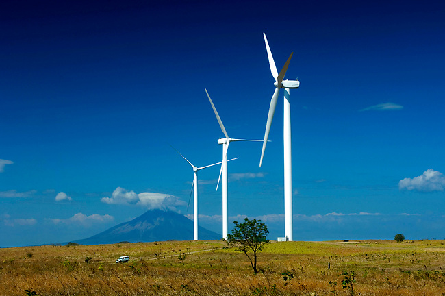 Wind turbines on the shores of Lake Nicargua.  Concepcion Volcano can be seen in the background rising on the Island Of Ometepe.