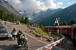 The Bernina Express runs next to the highway and crosses the highway at some points. Here you can see motorcyclists and cars waiting for the Bernina Express to pass with the Piz Bernina in the background, which is the highest mountain of the Eastern Alps at 4,049 meters; The Bernina Express is the highest altitute transalpine railway and one of the steepest railways