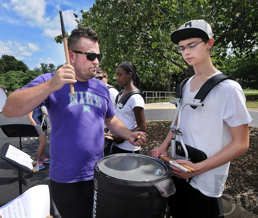STAFF PHOTO BEN GOFF  @NWABenGoff -- 07/09/14 Alex Miller, left, battery technician for the Bentonville High School marching band and a percussion major at the University of Arkansas, works one-on-one with second-chair snare drummer Jordan Bullock, 15, during drumline practice at Bentonville High School on Wednesday July 9, 2014.