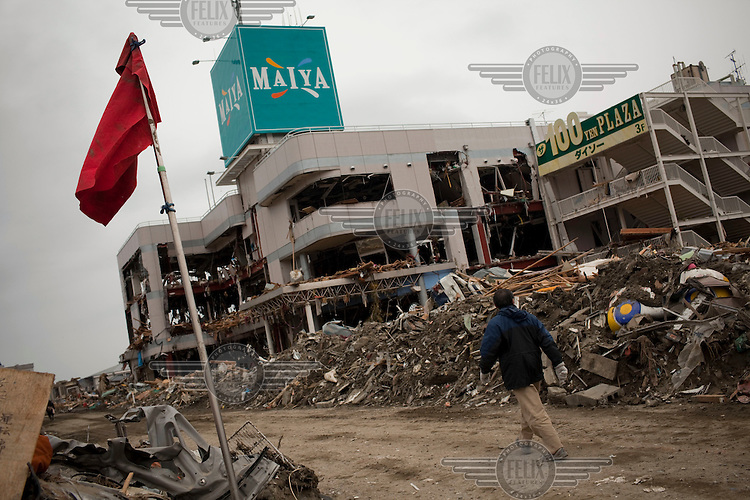 A man walks past a damaged multi-story shopping centre. Thousands of people died in this small town which ran out of body bags. On 11 March 2011 a magnitude 9 earthquake struck 130 km off the coast of Northern Japan causing a massive Tsunami that swept across the coast of Northern Honshu. The earthquake and tsunami caused extensive damage and loss of life.